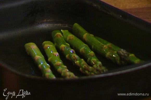 Спаржу выложить в глубокий противень, сбрызнуть оливковым маслом и отправить на 3–4 минуты под гриль.