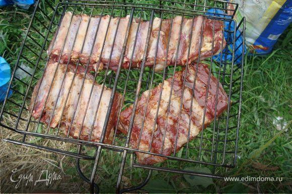 На решетку гриль выложить ребра и снова с обеих сторон кондитерской кисточкой смазать хорошо медом.
