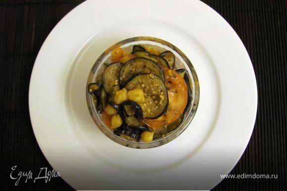 Горох нут замочить и сварить. Баклажаны промыть и тонко нарезать на кружочки. Поджарить их на хорошо прогретой, сухой сковороде. Помидоры промыть и нарезать тонкими кружочками. Приготовить заправку: смешать оливковое масло, уксус, горчицу, сухие травки, соль и перец. Соединить все ингредиенты и подавать.