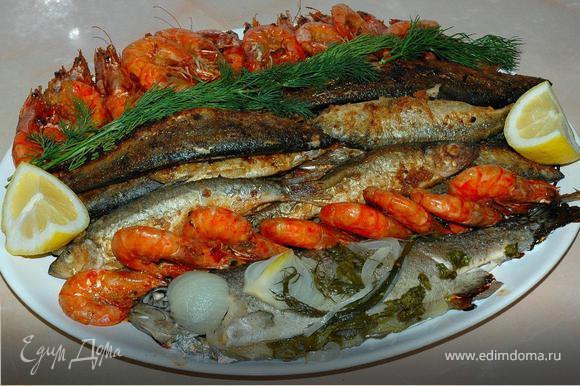 Готовим рыбную тарелку. Подготовленные тушки «Дорады» завернуть в фольгу, смазанную оливковым маслом. Разогреть духовку до 180 градусов. Запечь рыбу в фольге в течение 30-40 минут. Готовую рыбу вынуть из фольги и выложить на большое блюдо и слегка полить лимонным соком. «Салаку» обвалять в муке и обжарить с двух сторон на растительном масле до золотистой корочки. Выложить в центр блюда рядом с «Дорадой». Подготовленные креветки обжарить на сковородке в маринаде 10 минут на сильном огне, при необходимости добавить немного оливкового масла. Обжаренные креветки выложить по краям рыбной тарелки. Украсить блюдо свежей зеленью и дольками лимона.