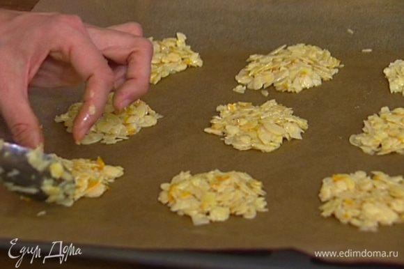 Выстелить противень бумагой для выпечки, смазанной маслом, и на большом расстоянии друг от друга ложкой выложить на бумагу небольшие печеньица, слегка расплющив их.
