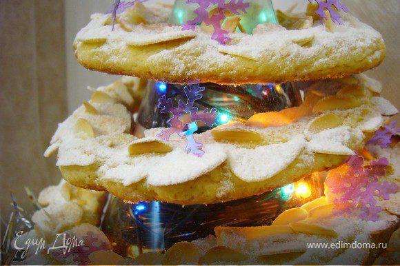 Во внутрь пластикового конуса я поместила новогоднюю гирлянду и украсила низ елки серебристой мишурой. Когда печенье остыло, я нанизала их на конус.