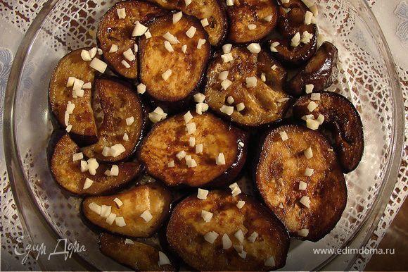 Готовые баклажаны выкладываем на блюдо в один слой и посыпаем рубленым чесноком.