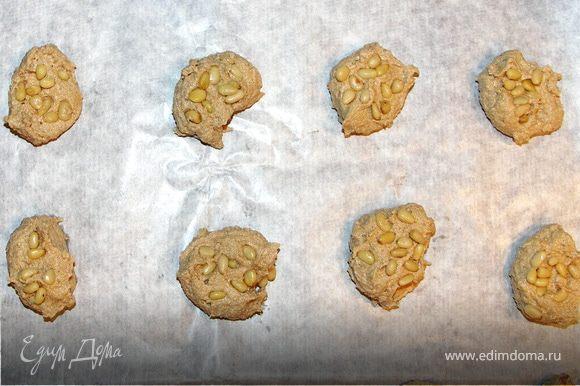 Лопаткой вмесить половину орешков.Ложкой выложить тесто на противень застланный бумагой для выпечки.Сверху присыпать оставшимися орешками.