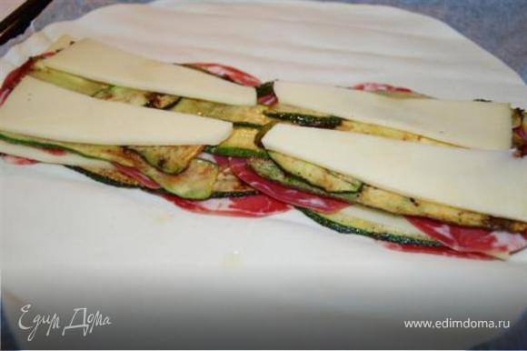 Тесто немного раскатать выложить на противень покрытый пергаментной бумагой. На тесто положить поочередно бекон, цукини, сыр.