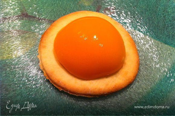 Когда кружки немного остынут, положить на каждый кружок половинку персика