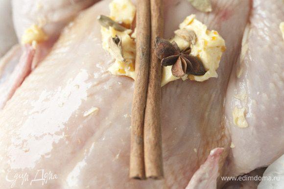 Получившейся смесью натереть тушку курицы изнутри и снаружи. Половину корицы, бадьяна и кардамона уложить внутрь курицы.
