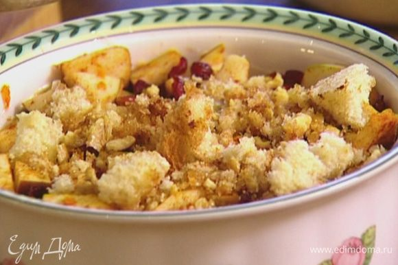 Покрошить оставшийся кусок батона, влить оставшееся растопленное масло, добавить сахар, орехи и корицу, перемешать и выложить сверху на яблоки.
