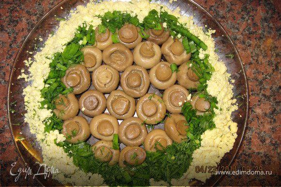 В центр блюда выложить шампиньоны шляпками вниз. Вокруг выложить мелко нарезанную зелень , Яичный желток вокруг зелени.