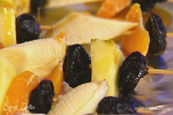 На каждую шпажку нанизать 1 курагу, кусочек ананаса, 1 чернослив, кружок банана, дольку мандарина и опять чернослив.