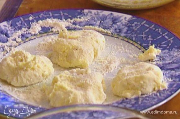 Влажными руками выкладывать кусочки теста на тарелку с мукой и формировать небольшие пирожки.