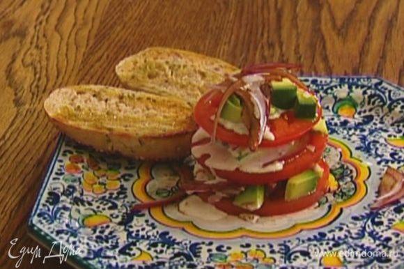 Булочку разрезать вдоль пополам, поджарить в тостере, затем слегка сбрызнуть оливковым маслом и подавать с башенкой из овощей.