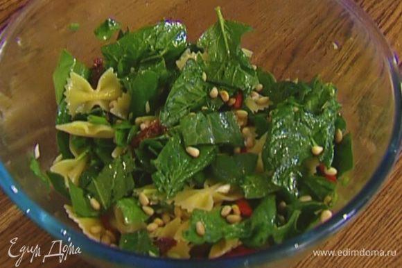 Добавить к макаронам шпинат, вяленые помидоры и зеленый лук, полить заправкой, присыпать кедровыми орехами. Подавать салат теплым или холодным.