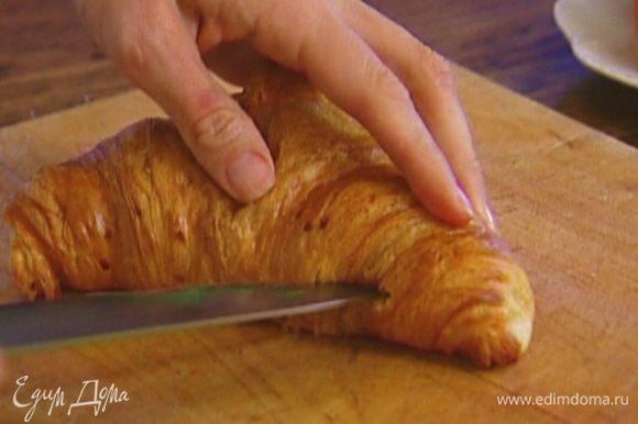 Круассаны отправить в разогретую духовку на пару минут и, пока они теплые, разрезать вдоль пополам.