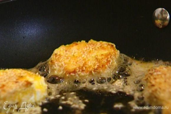 Кусочки сыра обмакнуть в яйцо, обвалять сначала в муке, затем в кунжуте, выложить в сковороду и обжарить до золотистого цвета.