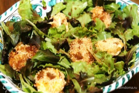 Салатный микс выложить в глубокую салатницу, полить половиной заправки, сверху выложить кусочки козьего сыра и полить оставшейся заправкой.