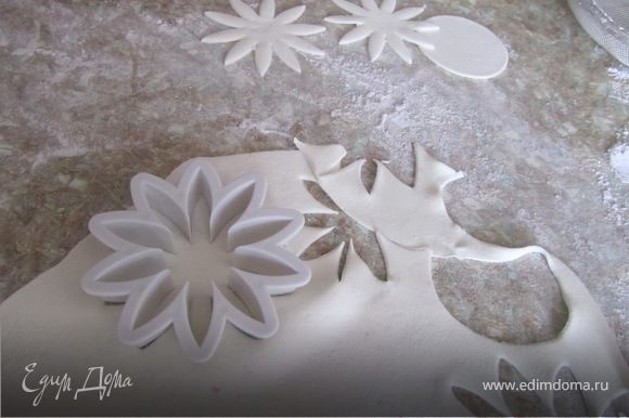 Раскатать мастику толщиной примерно 2 мм. Вырезать формочкой цветочки.