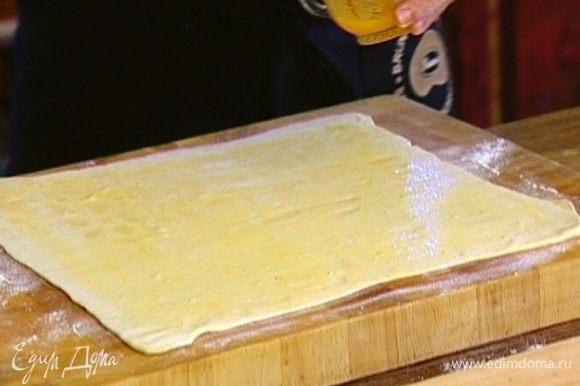 Слоеное тесто раскатать и промазать всю поверхность желтком.