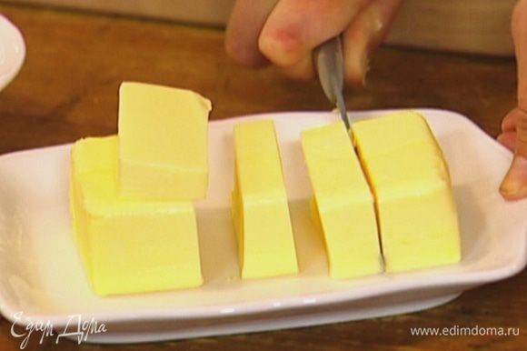 Сливочное масло нарезать кусочками и отправить к теплому медовому сиропу.