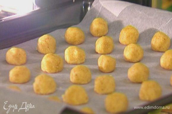 Отщипывая по маленькому кусочку теста, сделать небольшие шарики, выложить их на противень и отправить на 10–15 минут в разогретую духовку.