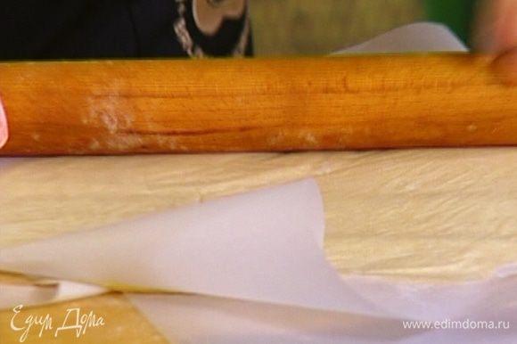Тесто вынуть из холодильника, поместить между двух листов бумаги для выпечки и раскатать скалкой в пласт, а затем прямо в бумаге опять отправить в холодильник.