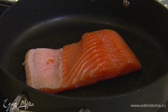 Разогреть в сковороде, которую можно ставить в духовку, 1 ч. ложку оливкового масла, выложить рыбу кожей вниз и обжаривать в течение 2–3 минут.