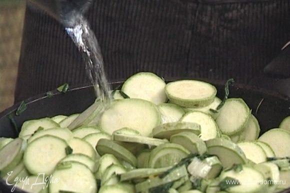 Добавить кабачки, влить 200 мл горячей воды, накрыть крышкой и оставить томиться на медленном огне 15−20 минут.
