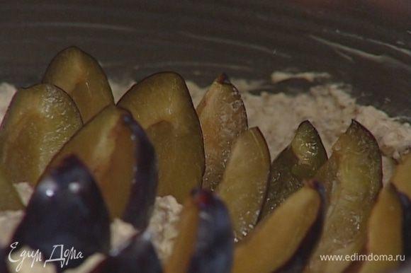 Начиная от центра, воткнуть в тесто дольки слив, наполовину погружая их в тесто (постараться разместить как можно больше слив).