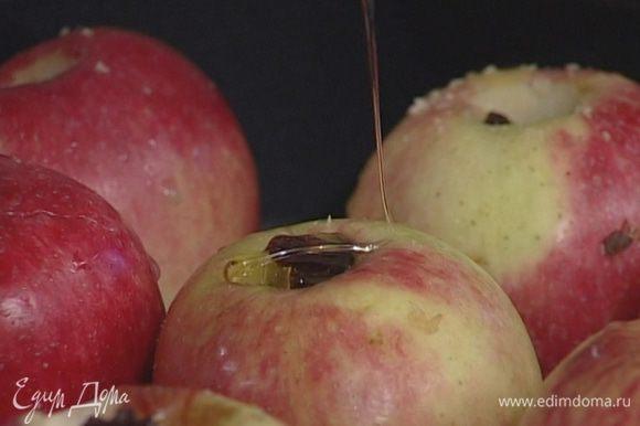 Начинить яблоки орехами, изюмом, добавить по 1 ч. ложке меда.