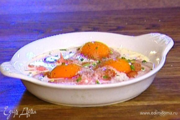 Шнитт-лук мелко нарезать, посыпать им яйца, посолить, поперчить и отправить форму в разогретую духовку на 8–10 минут.