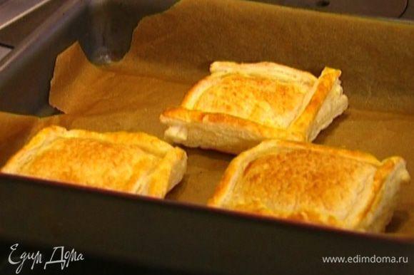 Противень застелить бумагой для выпечки и выложить туда квадраты из теста. Вилкой наколоть тесто в нескольких местах и поставить на 10 минут в разогретую духовку.