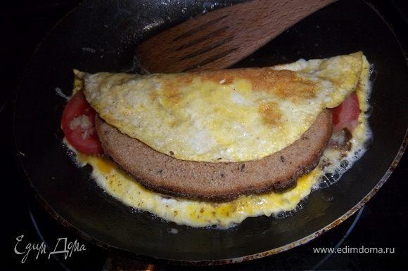 Сверху наркрыть свободной половиной омлета и жарить еще 2-3мин. до готовности