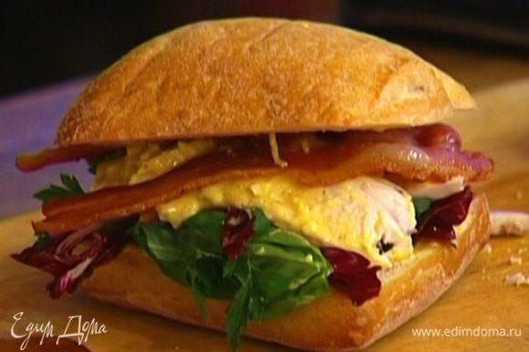 Радиккио порезать, соединить с петрушкой и базиликом (зелень резать не надо!), уложить на один кусок хлеба, сверху выложить курицу с заправкой и бекон, накрыть вторым куском хлеба.