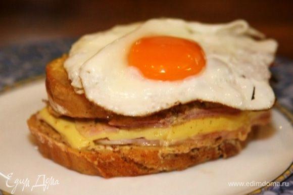 Выложить на тарелку бутерброд, а на него жареное яйцо.
