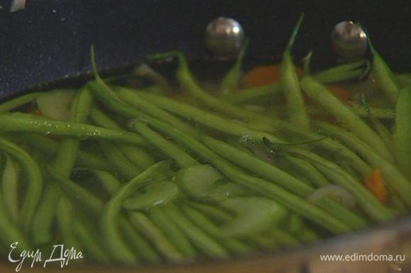 Добавить фасоль, перемешать овощи, залить горячим, подсоленным овощным бульоном, довести до кипения, накрыть крышкой и варить на небольшом огне 15 минут.