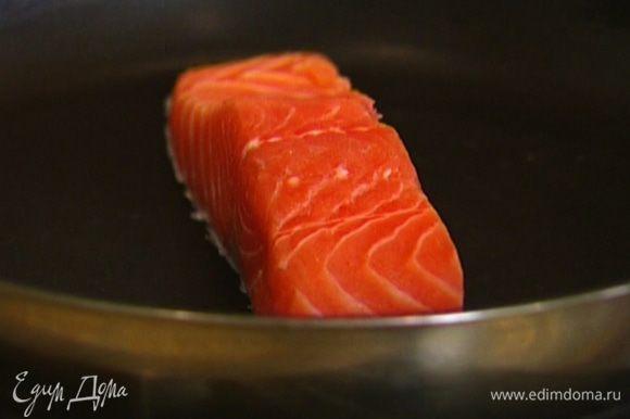 Разогреть сухую сковороду, выложить на нее семгу кожей вниз и готовить, пока нижняя часть рыбы не посветлеет, затем отправить сковороду в духовку на 5–7 минут.