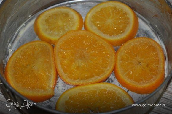Апельсины порезать кружечками, залить водой, всыпать сахар и поставить на огонь. Довести до кипения и варить на медленном огне 20 минут. Сироп слить. Выбрать самые красивые кружечки и уложить их на дно смазанной маслом разъемной формы (20-22 см. в диаметре).