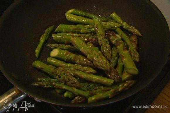 Переложить грибы в другую посуду, в сковороде разогреть еще 1 ст. ложку оливкового масла и обжарить верхушки спаржи, посолив и поперчив их.