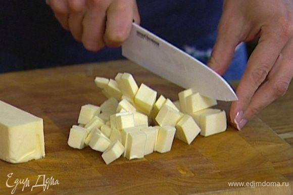 Предварительно охлажденное сливочное масло порубить кубиками.