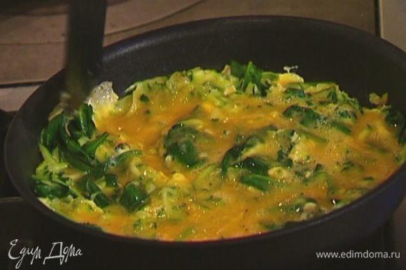 Влить в сковороду с цукини и шпинатом взбитые яйца и готовить 3 минуты, затем поместить на 2 минуты под гриль.