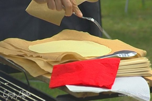 Разделить тесто на небольшие части, раскатать каждую часть в тонкую лепешку. Смазать листы бумаги для выпечки оливковым маслом и уложить лепешки друг на друга между смазанными листами бумаги.