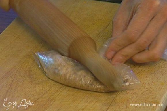 Печенье положить в пакет и измельчить скалкой.