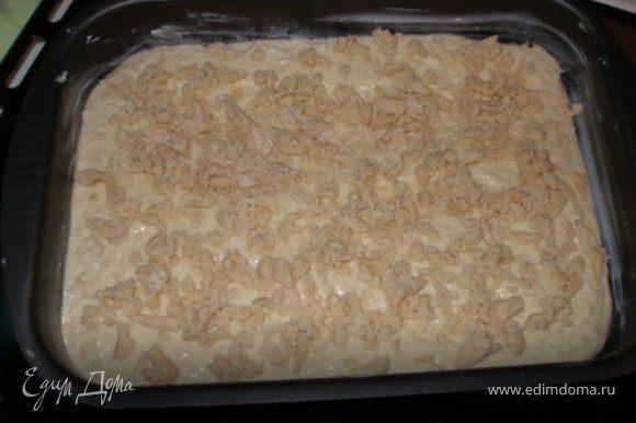 Форму смазать маслом, выложить тесто, сверху - посыпка.