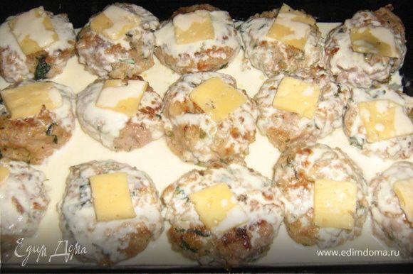 Выложить тефтели на смазанный маслом противень. Сыр нарезать тонкими ломтиками по размеру тефтели. Смешать йогурт и сливки, добавить специи. Залить соусом тефтели.