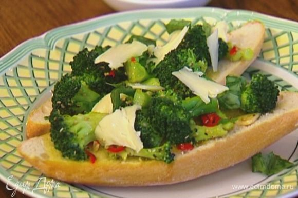На обжаренные ломтики хлеба выложить брокколи, присыпать сырными хлопьями и украсить листьями базилика.