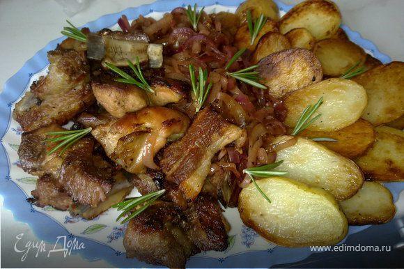 Выложить на блюдо ребра, лук и печеный картофель. Сверху выложить листики розмарина.