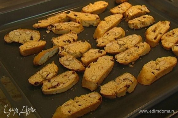 Нарезать батончики из теста наискосок, пока они горячие, и выложить на чистый сухой противень срезами вверх. Отправить бискотти в духовку еще на 2–3 минуты.