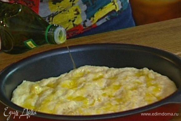 Подошедшее тесто обмять руками, выложить в смазанную маслом форму для выпечки, равномерно распределить, сбрызнуть оливковым маслом.