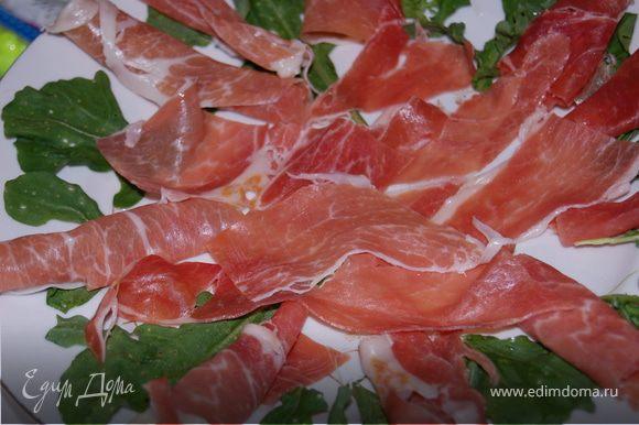 На тарелку выкладываем красиво листья руколы, предворительно вымыв ее и просушив.
