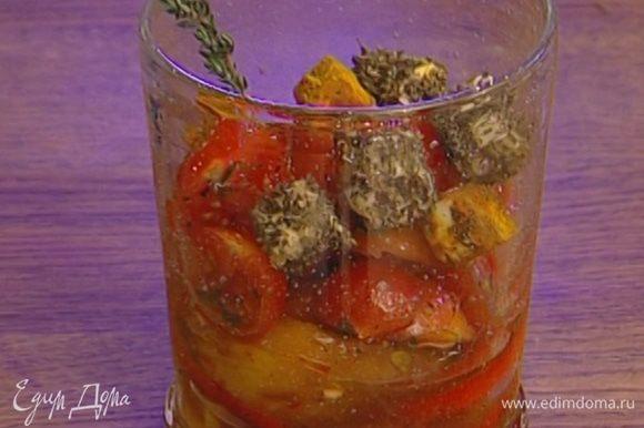 В широкие прозрачные стаканы выложить понемногу перца, затем по нескольку половинок помидоров, а сверху разноцветные кубики феты. Украсить веточками тимьяна.